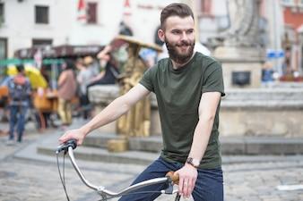 Souriant jeune homme à vélo en ville