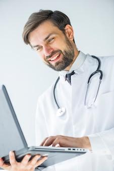 Souriant médecin naviguant sur ordinateur portable