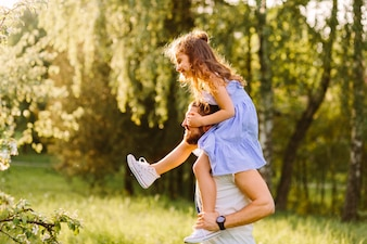 Souriant père portant sa fille sur les épaules