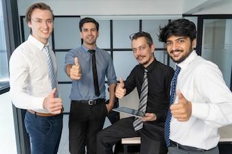 Sourire équipe commerciale réussie montrant pouce en l'air.