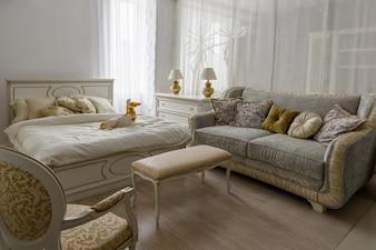 Statuette chien sur lit avec des draps blancs dans une chambre élégante