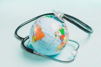 Stéthoscope sur le globe sur fond bleu