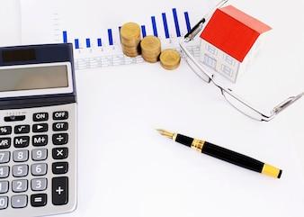 Stylo-plume et papier maison et pièces de monnaie et lunettes et calculatrice
