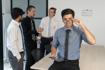 Succès jeune manager posant lors d'un briefing d'entreprise.