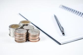 Sur la table des hommes d'affaires ont carnet, stylo et pile de pièces de monnaie.