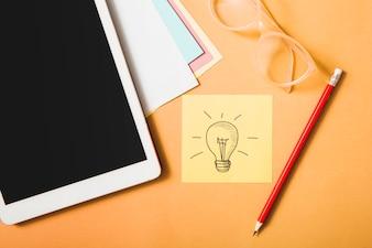 Symbole d'idée; crayon; lunettes; tablette numérique et papier carte sur fond orange