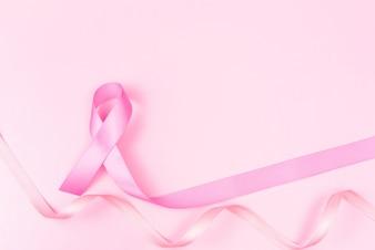 Symbole de ruban rose pour le concept de sensibilisation au cancer du sein sur fond rose avec copie SAV