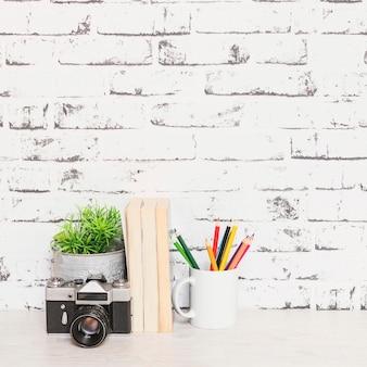 Table avec des livres caméra et des stylos près du mur