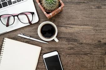 Table de bureau en bois marron avec un livre, un stylo, des cactus et un téléphone pour travailler