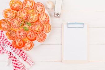 Table de cuisson avec assiette de tomates et presse-papiers