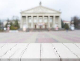 Table en bois blanche devant la façade floue d'un bâtiment public classique