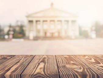 Table en bois devant la façade floue d'un bâtiment public classique