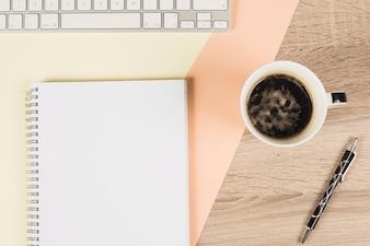 Tasse à café; stylo; clavier; et cahier à spirale sur fond coloré et en bois