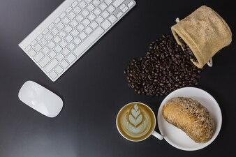 Tasse blanche de café et haricots sur fond noir