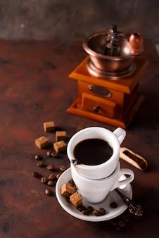Tasse de café chaud à la vapeur avec grains de café, moulin à café et sac de grains de café