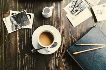 Tasse de café se trouve sur la table en bois parmi toutes les photos