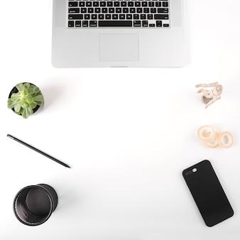 Tasse en plastique; portable; bande de violoncelle; téléphone portable; crayon; plante en pot; figurine sur la surface blanche