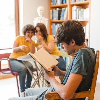 Teen boy reading book près de camarades de classe bavardage