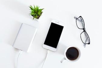 Téléphone portable connecté avec chargeur de banque d'alimentation avec des lunettes et une tasse de café sur fond blanc