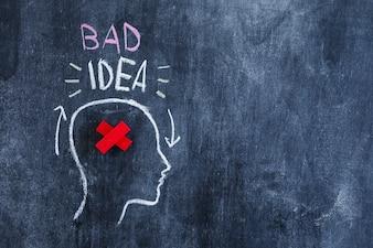 Texte de mauvaise idée sur la tête avec le rouge traversé dans la tête dessiné sur le tableau noir