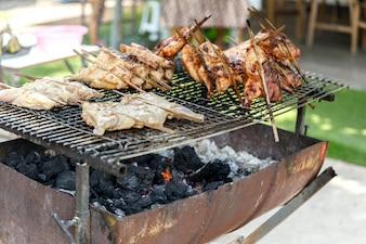 Thai Street Food: Charbon de bois Poulet rôti grillé sur le réservoir d'huile à moitié coupé.