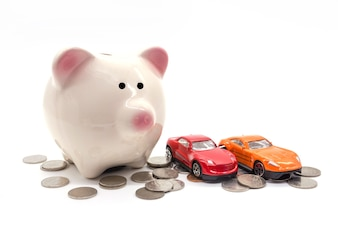 Tirelire avec voiture et pièce de monnaie sur fond blanc