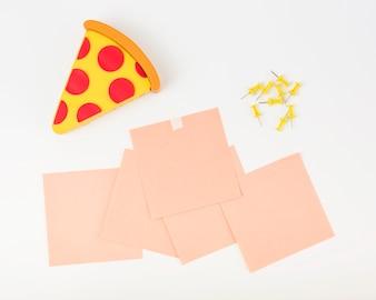Tranche de pizza; notes adhésives et punaises sur fond blanc
