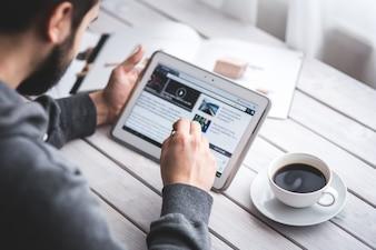 Travailleur la lecture des nouvelles avec la tablette