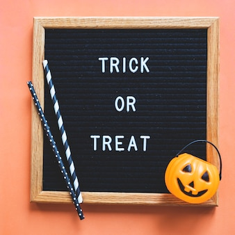 Trick ou traiter le panier et les pailles sur le cadre avec l'écriture