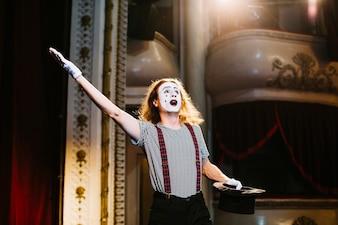 Un artiste mime masculin joue sur scène avec un chapeau dans l'auditorium