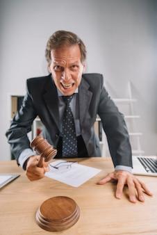 Un avocat en colère mature frappe un maillet sur un bloc dans la salle d'audience