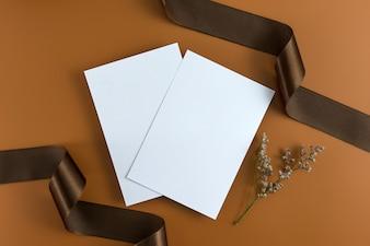 Un concept de mariage. Invitation de mariage sur fond marron avec ruban.