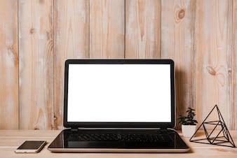 Un ordinateur portable ouvert avec écran blanc et téléphone portable sur une table en bois