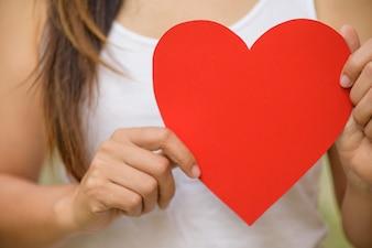 Une femme tient un grand papier de cœur rouge fait à la main. Saint Valentin, concept d'amour.