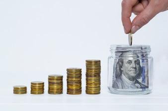Une main met une pièce dans un pot avec des dollars