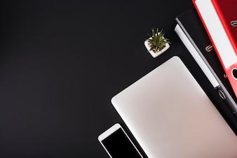 Une vue aérienne d'un téléphone cellulaire; portable; plante de cactus et fichiers sur fond noir