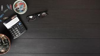 Une vue aérienne de trombones colorés; calculatrice et lunettes sur une table en bois noire