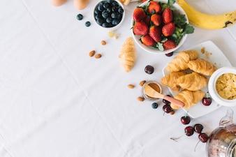 Une vue de dessus de fruits frais et croissant sur la table à manger