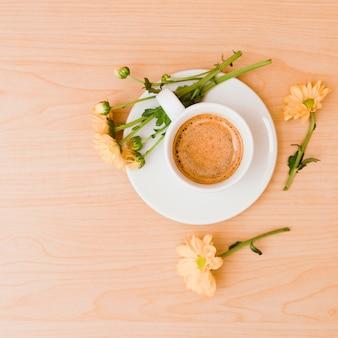 Une vue de dessus de la tasse à café et une soucoupe avec des fleurs couleur pêche sur fond texturé en bois