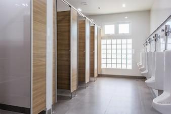 Urinoirs blancs dans la salle de toilette publique des hommes propres vides avec une grande fenêtre et une lumière extérieure