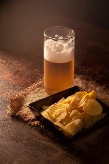 Verre de bière et de pommes chips sur une table en bois