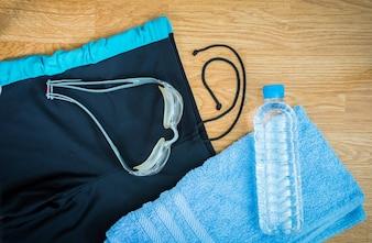 Verres et caleçons de bain, bouteilles d'eau, serviette