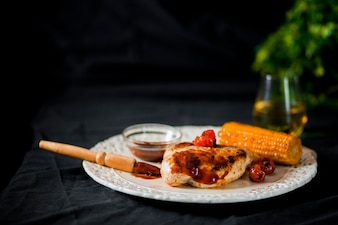 Viande de porc avec tomate cerise et maïs sur plaque