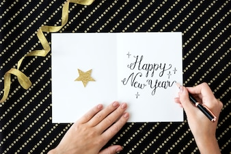 Vue aérienne, closeup, de, main, écriture, nouvel an, souhait, sur, carte