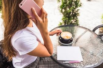 Vue aérienne, de, femme, conversation téléphone portable, tenue, tasse café