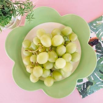 Vue aérienne de raisins verts frais sur une plaque en forme de fleur