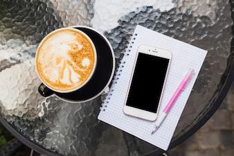 Vue aérienne du café avec un téléphone portable sur un carnet et un stylo