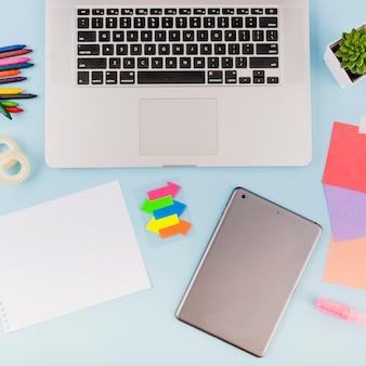 Vue aérienne du clavier d'ordinateur portable; tablette numérique et; page blanche et symbole de flèche colorée sur fond bleu