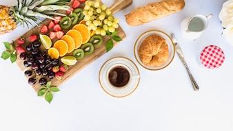 Vue aérienne du petit déjeuner sain avec assortiment de fruits, thé et pain