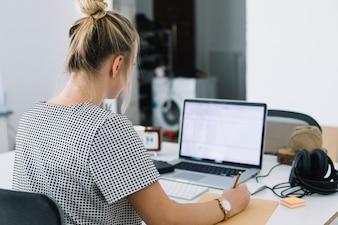 Vue arrière d'une femme d'affaires écrit des notes sur du papier brun avec un ordinateur portable sur le bureau